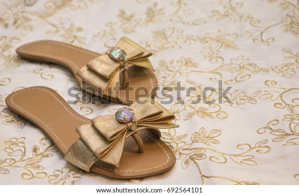 Golden sandals flip-flops decorated with a bow and glass on a background of fabric with a gold pattern