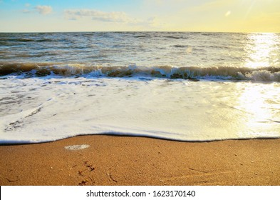 Golden sandy beach on the Bakal Spit on the Black Sea in Crimea. Wide foamy wave and sunny walkway background.