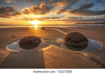 Golden scene sunrise at Moeraki Boulders beach. Coastal landscape of South Island New Zealand. Famous Place.
