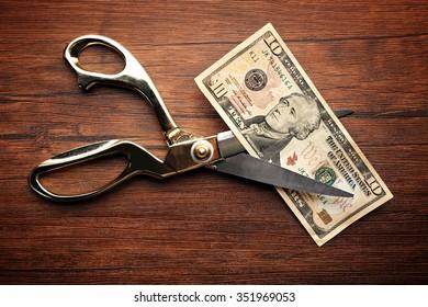 Golden scissors cut money on wooden background