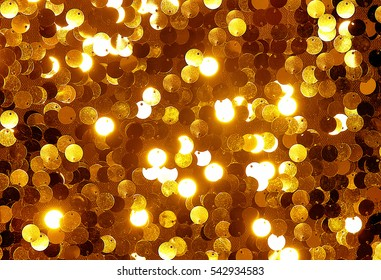 Golden sequins shimmering shining sparkling sequined textile