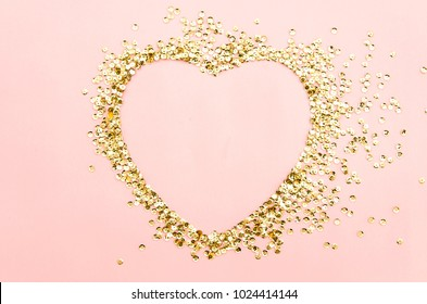 golden sequins shining paillettes heart shapeep on a pink paper background. Template for card, invitation. Blank space for text. Valentines day flat lay mockup.