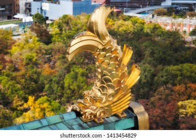Golden Shachi - Sculptural roof ornaments at Osaka Castle in Japan, a mythical creature with the head of a tiger and body of a carp, protectors of the castle. Osaka Castle Park View in autumn below.