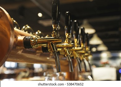 golden shiny beer taps in beer bar