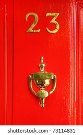 golden sign on red wooden door; 23 and cup; reflection in cup
