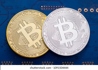 Golden and silver Bitcoin (BTC) cryptocurrency coin with computer chip in background
