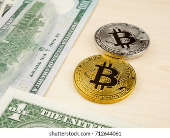 Golden and silver bitcoin coin on us dollars close up