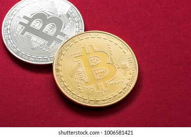 Golden and silver bitcoin isolated on red background.