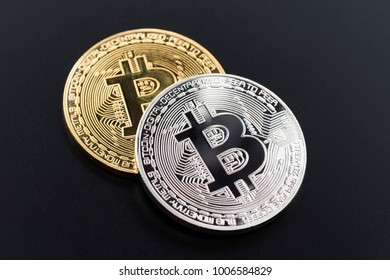 Golden and silver bitcoin isolated on black background.