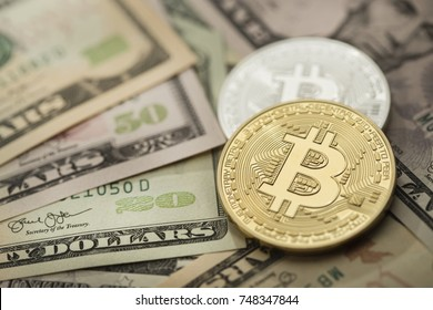 Golden and silver bitcoin over dollar bills. Fiat currency vs digital currency.