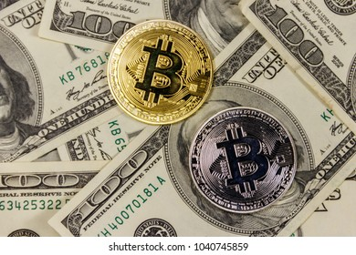 Golden and silver bitcoins on hundred dollar bills background