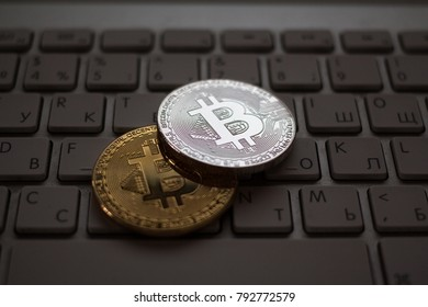 Golden and silver bitcoins on keyboard.