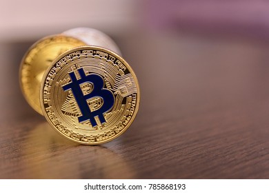 golden and silver bitcoins on wooden table