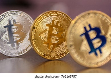 golden and silver bitcoins stands on wooden table
