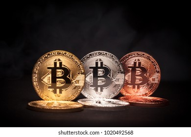 Golden, Silver and Bronze coloured Bitcoins over black