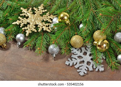 Golden and silver Christmas decorations and spruce branch on a wooden background