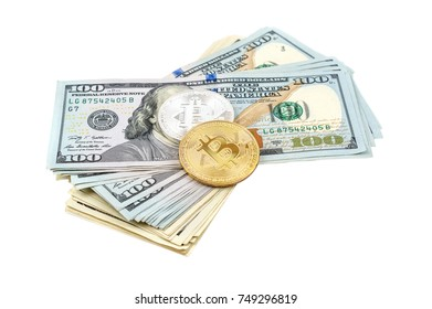 Golden and silver coins of bitcoin with heap of dollar bill on white. Business concept.