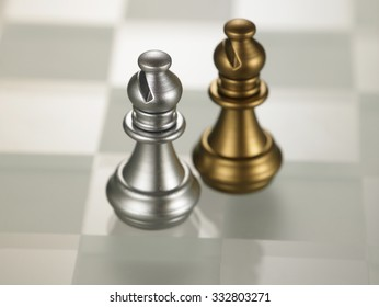 golden and silver color chess piece bishop on glass chess board