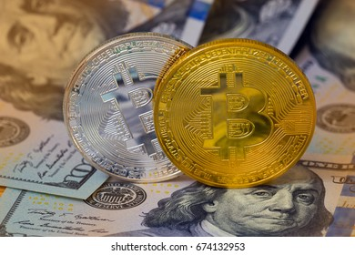 Golden and silver metal bitcoin on money background.