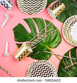 Golden and silver paper glasses, dishes and straws, horns and monstera leaves on a table.  Pink background. Party concept.