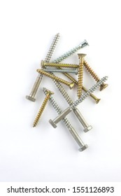 golden and silver screws lying on top of each other on a white background.vertical orientation.Flat lay
