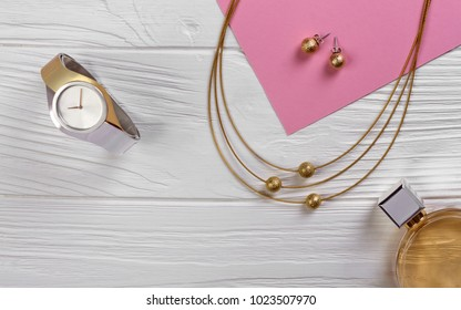 Golden and silver watch and golden necklace on white wooden background