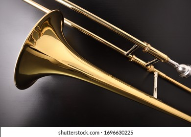 Golden slide trombone detail on black wooden table. Top view. Horizontal composition.