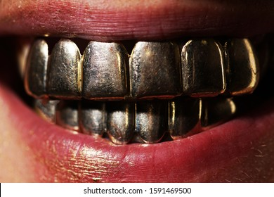 Golden smile. Man laughing in gold teeth. Expensive close up man smile with gold teeth. Gold metallic teeth. Mens golden smile close up