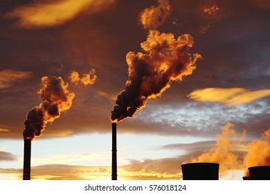 golden smoke from coal power plant during sunset