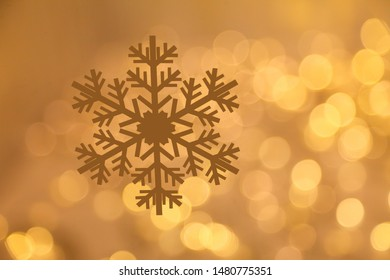 Golden snowflake with glittering bokeh background with copy space for Christmas and New Year celebration and greeting card design purpose