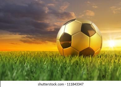 Golden Soccerball 3D on playing field under beautiful sundown