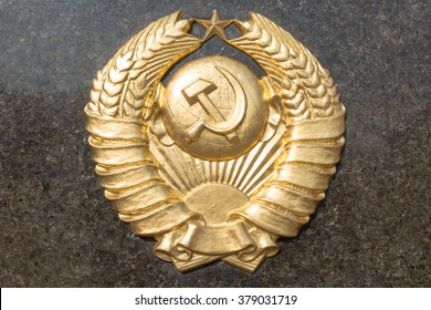 Golden soviet CCCP emblem with hammer and sickle on a marble plate