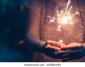 Golden sparkler held on hand at night with copy space for background use / vintage film tone