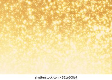 Golden sparkles or glitter lights. Festive gold background. Defocused circles bokeh or particles