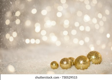 Golden Sparkling balls on Snow against Blurred Bokey lights Background: Christmas Holiday theme