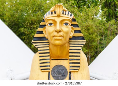 golden Sphinx statue with white pyramid building