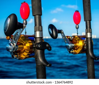 Golden sport fishing rod and reels set up for sailfishing off the coast of West Palm Beach, Florida. The blue line and golden reels mess beautifully with the blue Atlantic Ocean.