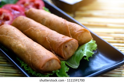 The golden spring roll set up with the green salad and red tomatoes