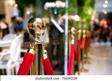 Golden stanchions with a red rope. Barrier, enclosed VIP area, protected enterance, private event, luxury gala concept.