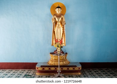 Golden standing buddha statue in front of a blue wall