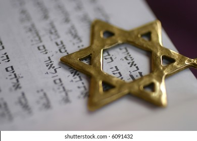 A Golden Star of David, a Jewish symbol, over the first word of the book of Genesis.