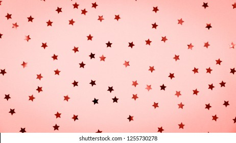 Golden star sprinkles on pink. Festive holiday background. Celebration concept. Top view, flat lay. Horizontal, wide screen format. Living coral theme - color of the year 2019