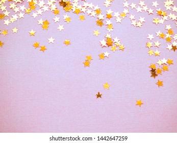 Golden stars glitter on lavender paper background. Festive holiday bright backdrop