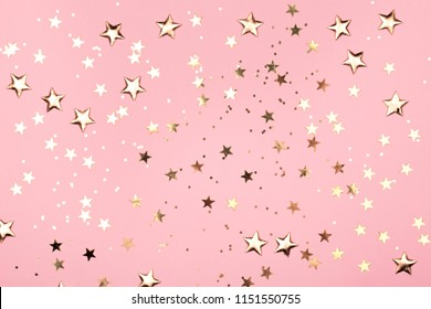 Golden stars glitter on pink background. Festive holiday pastel backdrop.