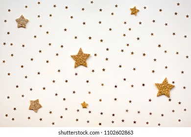 Golden stars glitter on yellow background. Festive holiday pastel backdrop.