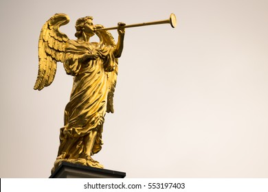 Golden statue of an angel with a trumpet and copy space.
