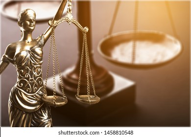 Golden statue of a fair lady against the scales of justice