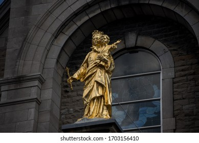 Golden statue of Mary and Baby Jesus in front of Church