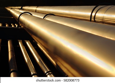 golden steel pipes in oil refinery during sunset