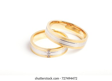 Golden striped wedding rings on pure white background.